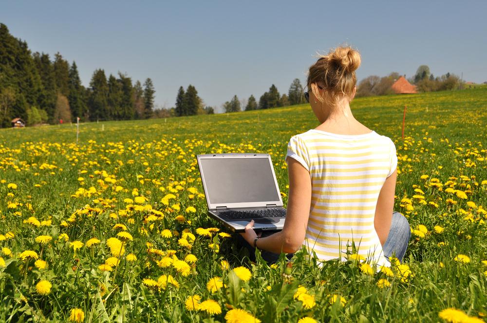 Frau-mit-Computer-in-Natur-shutterstock